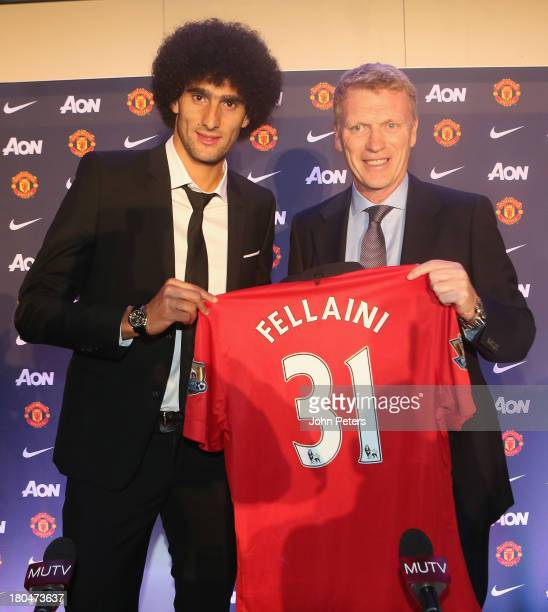 Marouane Fellaini of Manchester United poses with Manager David Moyes during a press conference to announce his signing at Old Trafford on September...