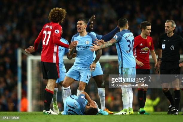 Marouane Fellaini of Manchester United reacts after clashing heads with Sergio Aguero of Manchester City during the Premier League match between...