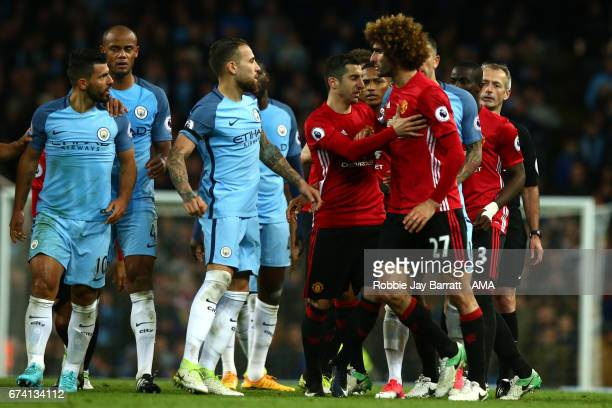 Marouane Fellaini of Manchester United reacts to Sergio Aguero of Manchester City after being sent off during the Premier League match between...