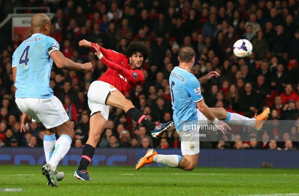 <a gi-track='captionPersonalityLinkClicked' href=/galleries/search?phrase=Marouane+Fellaini&family=editorial&specificpeople=3936316 ng-click='$event.stopPropagation()'>Marouane Fellaini</a> of Manchester United shoots at goal under pressure from Pablo Zabaleta of Manchester City during the Barclays Premier League match between Manchester United and Manchester City at Old Trafford on March 25, 2014 in Manchester, England.