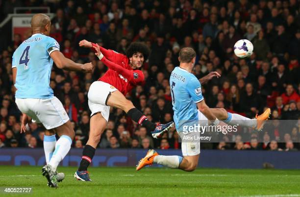 Marouane Fellaini of Manchester United shoots at goal under pressure from Pablo Zabaleta of Manchester City during the Barclays Premier League match...
