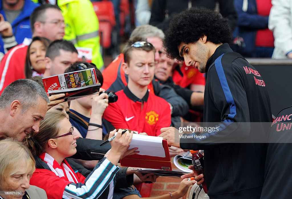 Marouane Fellaini of Manchester United signs autographs prior to the Barclays Premier League match between Manchester United and Crystal Palace at Old Trafford on September 14, 2013 in Manchester, England.
