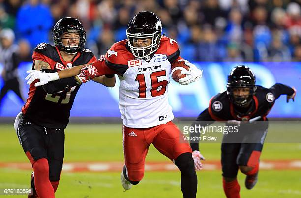 Marquay McDaniel of the Calgary Stampeders fends off Mitchell White of the Ottawa Redblacks during the first half of the 104th Grey Cup Championship...