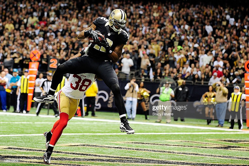 Marques Colston #12 of the New Orleans Saints catches a touchdown pass in front of Dashon Goldson #38 of the San Francisco 49ers during a game at the Mercedes-Benz Superdome on November 25, 2012 in New Orleans, Louisiana.