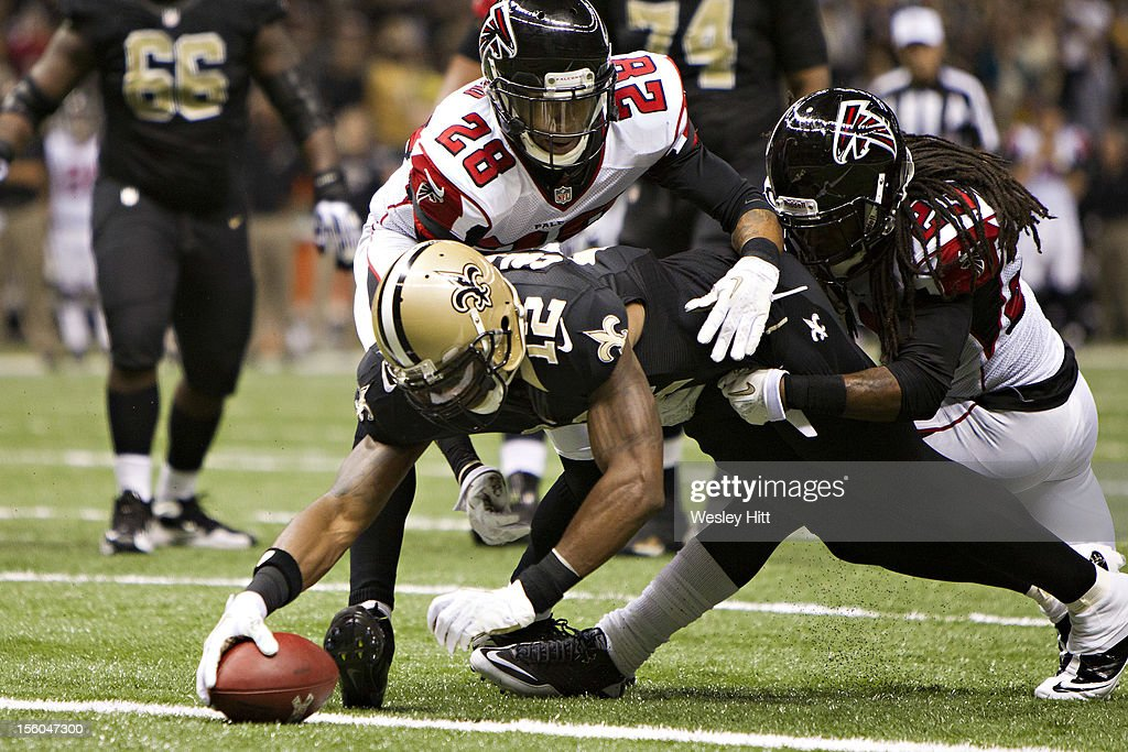 <a gi-track='captionPersonalityLinkClicked' href=/galleries/search?phrase=Marques+Colston&family=editorial&specificpeople=741430 ng-click='$event.stopPropagation()'>Marques Colston</a> #12 of the New Orleans Saints stretches for yardage while being held by <a gi-track='captionPersonalityLinkClicked' href=/galleries/search?phrase=Thomas+DeCoud&family=editorial&specificpeople=4037323 ng-click='$event.stopPropagation()'>Thomas DeCoud</a> #28 and <a gi-track='captionPersonalityLinkClicked' href=/galleries/search?phrase=Dunta+Robinson&family=editorial&specificpeople=182498 ng-click='$event.stopPropagation()'>Dunta Robinson</a> #23 of the Atlanta Falcons at Mercedes-Benz Superdome on November 11, 2012 in New Orleans, Louisiana. The Saints defeated the Falcons 31-27.
