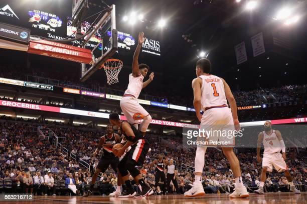 Marquese Chriss of the Phoenix Suns leaps over Evan Turner of the Portland Trail Blazers as he attempts a shot during the second half of the NBA game...