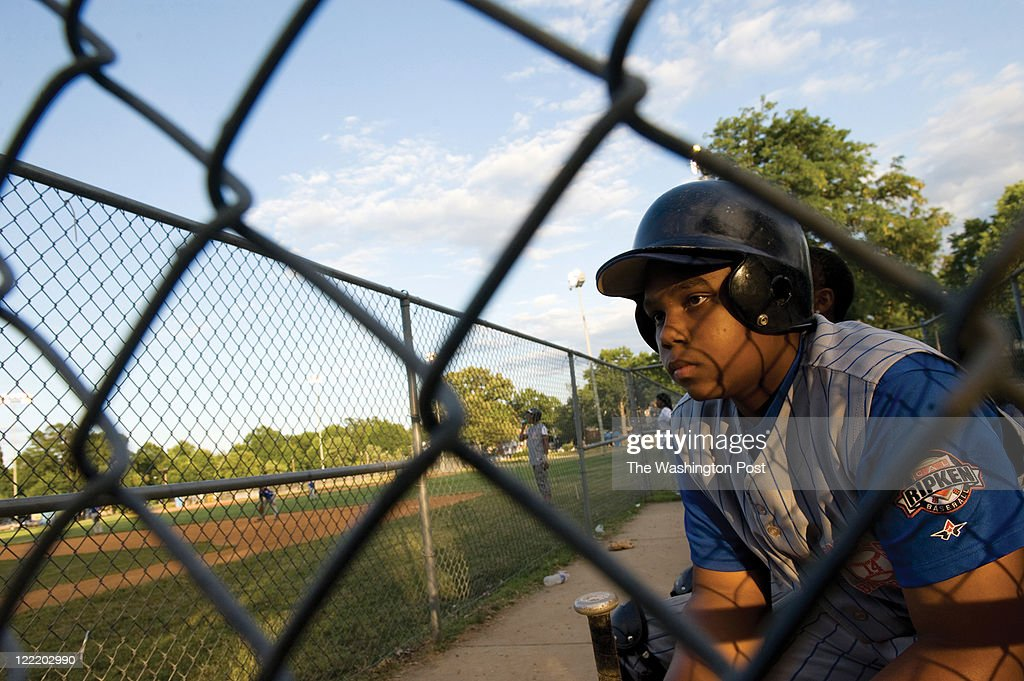 Marquette Henderson, right, waits for his turn to bat during a playoff game against the Takoma Rangers at the Taft Recreation Center on Tuesday June 14, 2011 in Washington, DC. The AYT #14 Raiders won 16-1. This game was in the Cal Ripken Division of the Babe Ruth League.