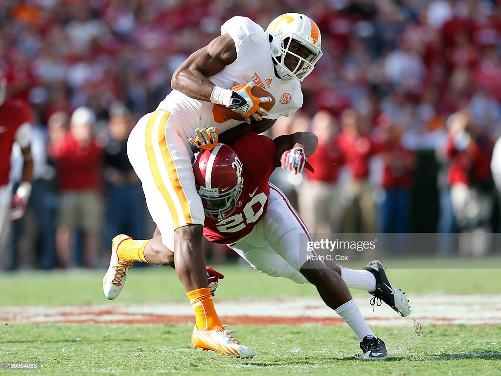 Marquez North #8 of the Tennessee Volunteers pulls in this reception as he is tackled by Jarrick Williams #20 of the Alabama Crimson Tide at Bryant-Denny Stadium on October 26, 2013 in Tuscaloosa, Alabama.