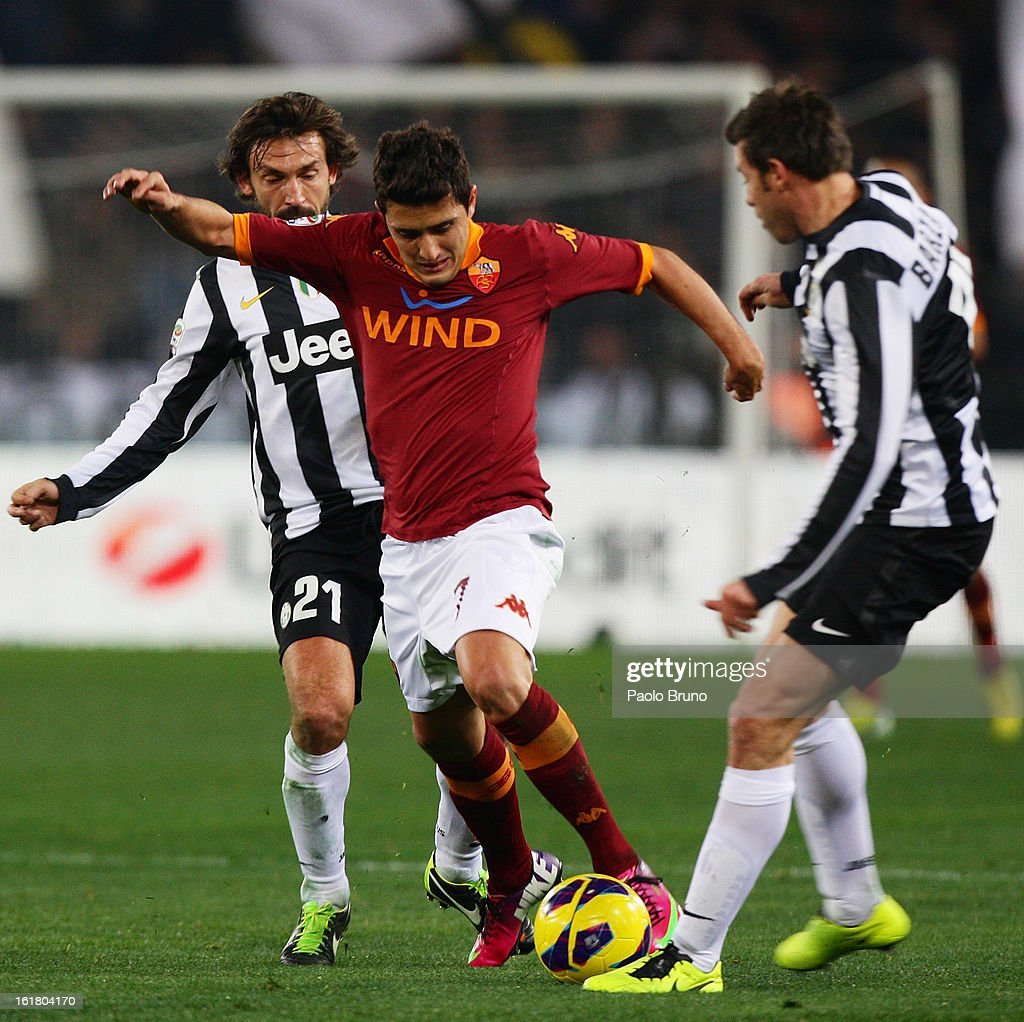 Marquinho (C) of AS Roma competes for the ball with Andrea Pirlo (L) and Andrea Barzagli of Juventus FC during the Serie A match between AS Roma and Juventus FC at Stadio Olimpico on February 16, 2013 in Rome, Italy.