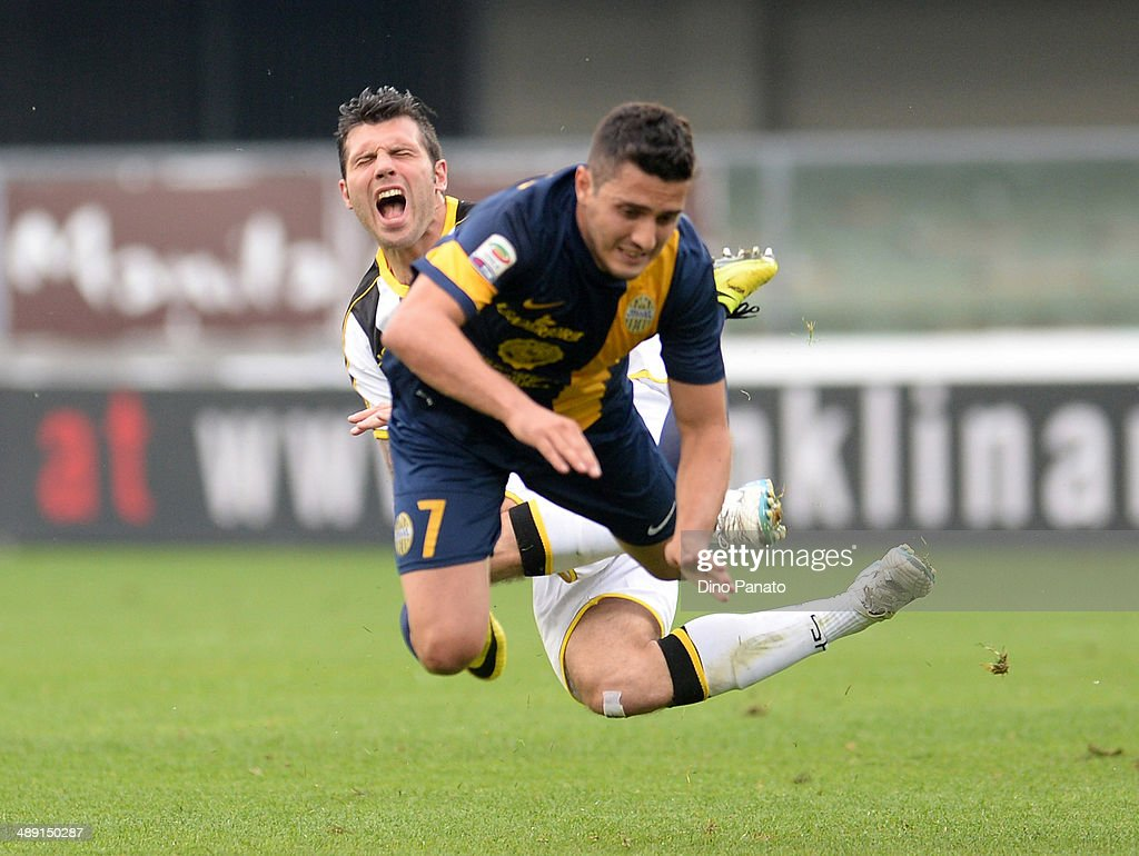 Marquinho #7 of Hellas Verona is tackled by <a gi-track='captionPersonalityLinkClicked' href=/galleries/search?phrase=Maurizio+Domizzi&family=editorial&specificpeople=790985 ng-click='$event.stopPropagation()'>Maurizio Domizzi</a> of Udinese Calcio during the Serie A match between Hellas Verona FC and Udinese Calcio at Stadio Marc'Antonio Bentegodi on May 10, 2014 in Verona, Italy.