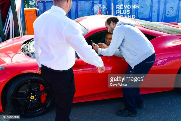 Marquinhos of PSG poses for a photo with a fan as he arrives for the first preseason training session of Paris SaintGermain on July 4 2017 in Paris...