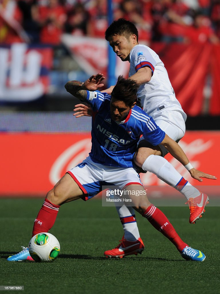 Marquinhos #18 (L) of Yokohama F.Marinos and <a gi-track='captionPersonalityLinkClicked' href=/galleries/search?phrase=Daiki+Iwamasa&family=editorial&specificpeople=1295487 ng-click='$event.stopPropagation()'>Daiki Iwamasa</a> #3 of Kashima antlers compete for the ball during the J.League match between Yokohama F.Marinos and Kashima Antlers at Nissan Stadium on May 3, 2013 in Yokohama, Kanagawa, Japan.
