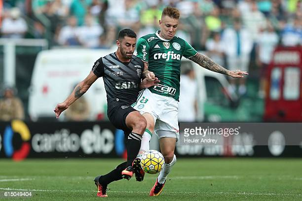 Marquinhos Pedroso of Figueirense struggles for the ball with Roger Guedes of Palmeiras during a match between Figueirense and Palmeiras as part of...