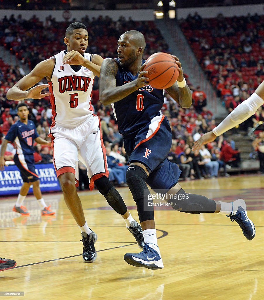 Marquis Horne #0 of the California State Fullerton Titans drives against Christian Wood #5 of the UNLV Rebels during their game at the Thomas & Mack Center on December 28, 2013 in Las Vegas, Nevada. UNLV won 83-64.