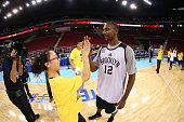 Marquis Teague of the Brooklyn Nets high fives a participant in the NBA Cares Basketball Skills Clinic as part of the 2014 NBA Global Games at the...