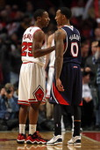 Marquis Teague of the Chicago Bulls talks to his older brother Jeff Teague of the Atlanta Hawks during a game at the United Center on January 14 2013...