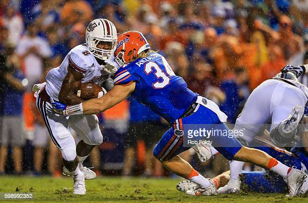 Marquis Young of the Massachusetts Minutemen in action against Alex Anzalone of the Florida Gators at Ben Hill Griffin Stadium on September 3 2016 in...