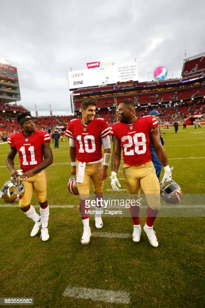 Marquise Goodwin Jimmy Garoppolo and Carlos Hyde of the San Francisco 49ers talk on the field following the game against the Seattle Seahawks at...