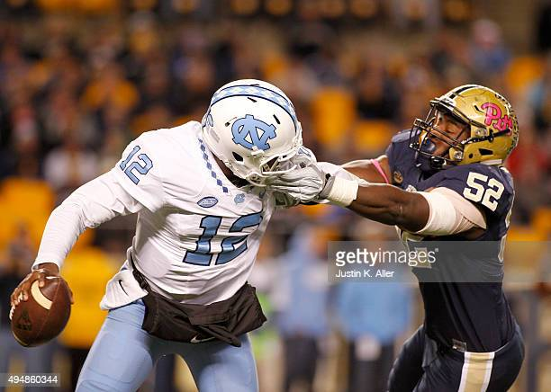 Marquise Williams of the North Carolina Tar Heels rolls out to pass and has his face mask grabbed by Shakir Soto of the Pittsburgh Panthers during...