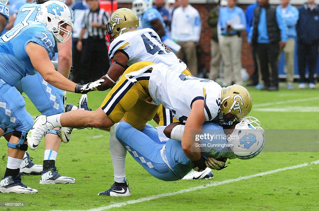 Marquise Williams of the North Carolina Tar Heels takes a hit from Adam Gotsis of the Georgia Tech Yellow Jackets on October 3 2015 in Atlanta...