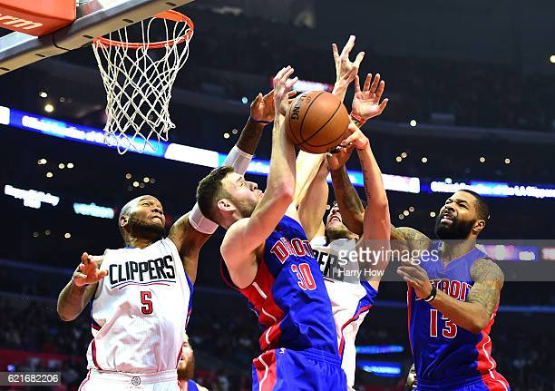 Marreese Speights and Austin Rivers of the Los Angeles Clippers reach for a rebound against Jon Leuer and Marcus Morris of the Detroit Pistons during...