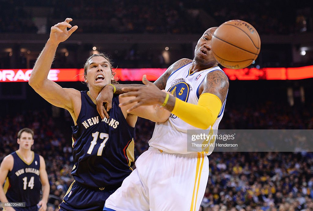 Marreese Speights #5 of the Golden State Warriors has the ball slapped out of his hands by Lou Amundson #17 of the New Orleans Pelicans at ORACLE Arena on December 17, 2013 in Oakland, California.