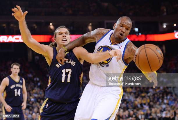 Marreese Speights of the Golden State Warriors has the ball slapped out of his hands by Lou Amundson of the New Orleans Pelicans at ORACLE Arena on...