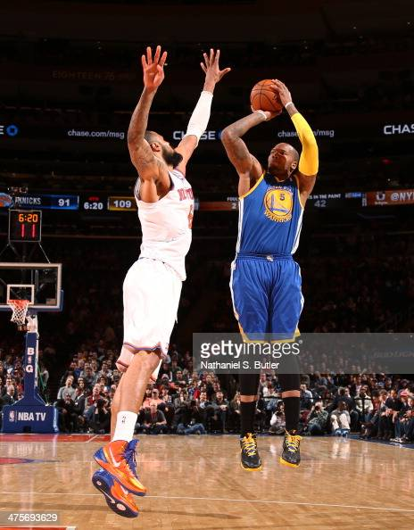 Marreese Speights of the Golden State Warriors shoots against Tyson Chandler of the New York Knicks during a game at Madison Square Garden in New...