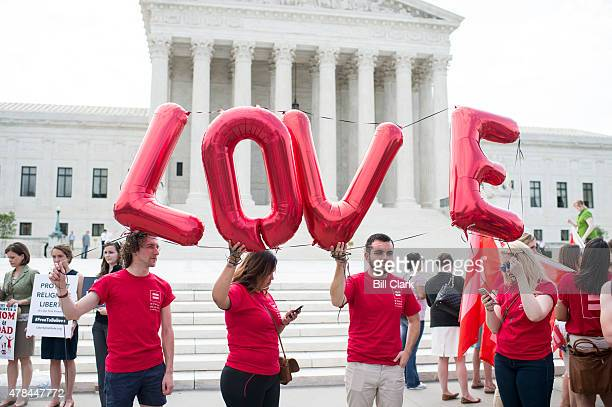 Marriage equality supporters hold up 'LOVE' balloons outside the Supreme Court as they check their phones for news on the pending court decision on...