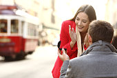 Vintage marriage proposal outdoors in the streets of portugal with a red tram in the background