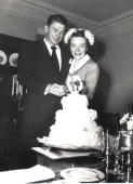 Married actors Ronald and Nancy Reagan cutting cake following their wedding ceremony