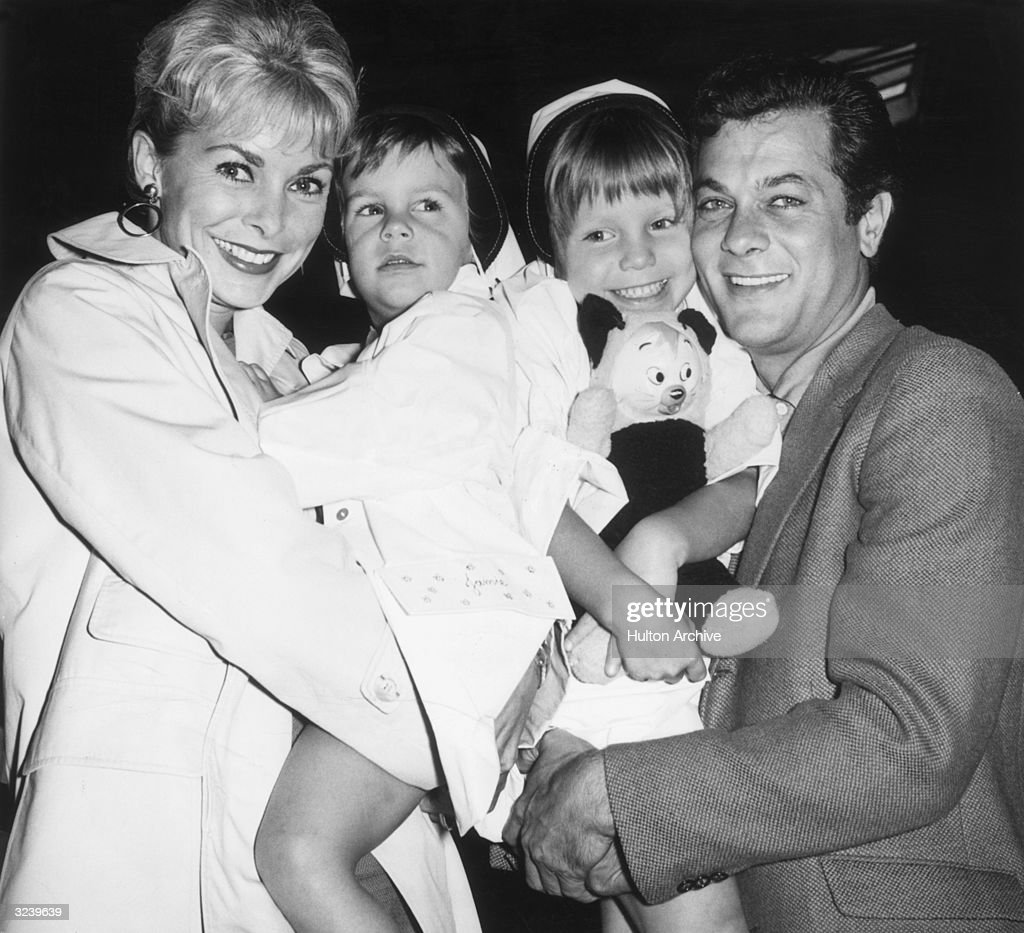 Married American actors Janet Leigh and Tony Curtis holding their daughters Kelly (right), 5, and Jamie, 2, prior to their departure on the SS 'Argentina,' bound for Argentina, where Curtis will work on location for director J Lee Thompson's film, 'Taras Bulba'. Kelly is holding a stuffed animal.