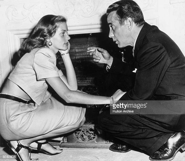Married American actors Lauren Bacall and Humphrey Bogart kneel in front of a fireplace in their home California Bogart is holding a cigarette and...