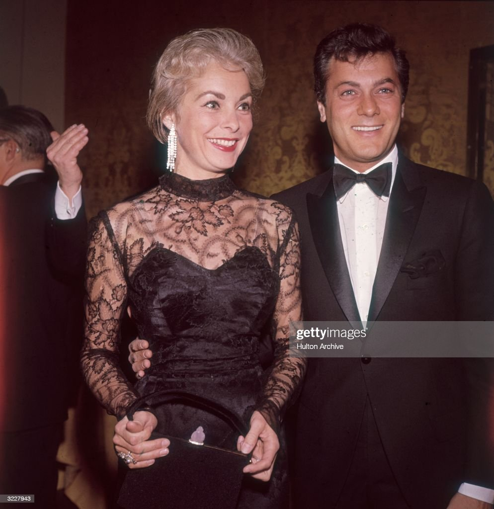 Married American actors Tony Curtis and Janet Leigh smiling while at a formal event. Curtis is wearing a black tuxedo. Leigh is wearing a black dress with a sheer lace top.