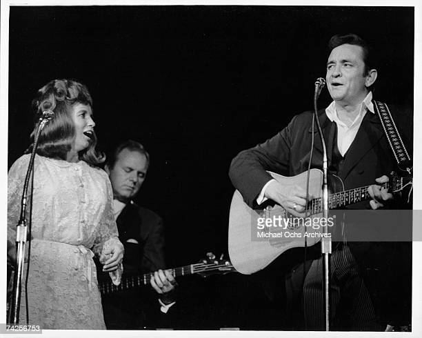 Married country singers Johnny Cash and June Carter Cash perform onstage in 1968 in Los Angeles California