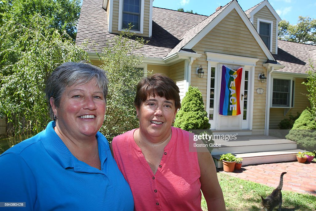 Married couple Lauri Ryding left and Cari Ryding pose with their replacement flag at their home in Natick Mass on Aug 22 after returning home from...