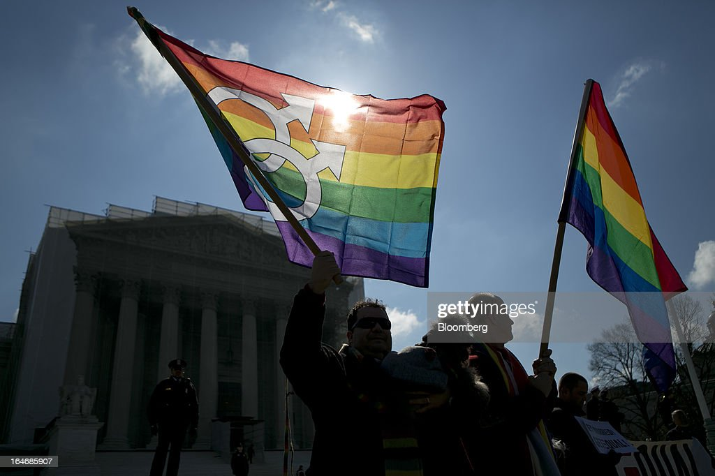 Married couple Marcos German-Domingues, left, and Daniel German Domingues from Massachusetts hold rainbow flags while demonstrating outside the U.S. Supreme Court in Washington, D.C., U.S., on Tuesday, March 26, 2013. The Supreme Court takes up what is probably its biggest civil-rights dispute in decades this week when it hears arguments that could lead to the legalization of same-sex marriage nationwide. Photographer: Andrew Harrer/Bloomberg via Getty Images