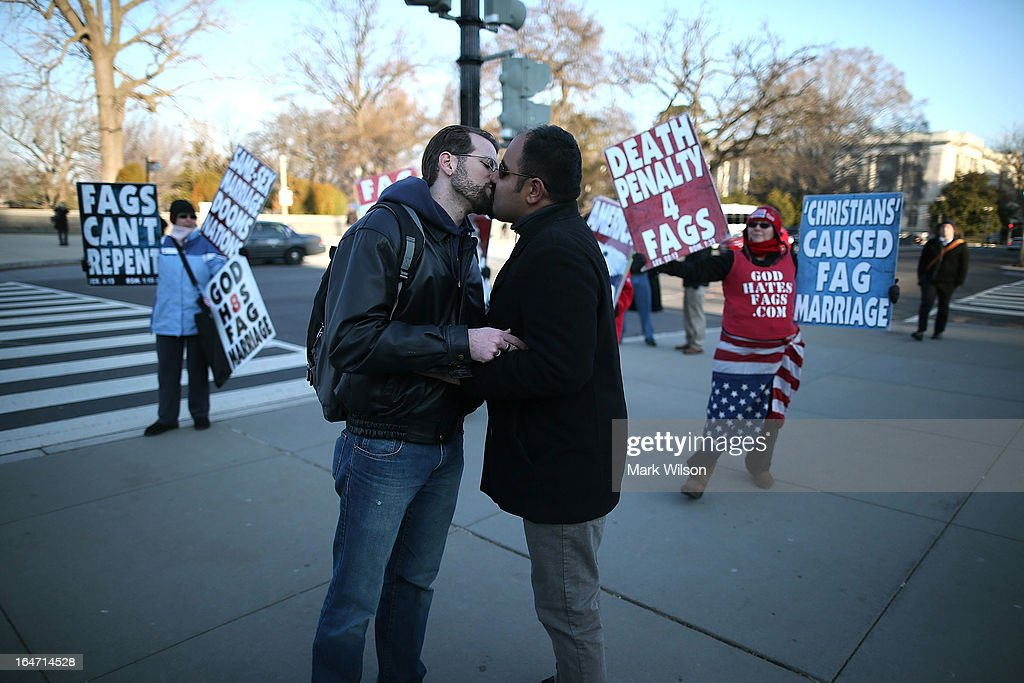 Married couple Nathan Lents (L) and Oscar Cifuentes kiss in front of Westboro Baptist Church protesters, in front of the U.S. Supreme Court, on March 27, 2013 in Washington, DC. Today the high court is scheduled to hear arguments on whether Congress can withhold federal benefits from legally wed gay couples by defining marriage as only between a man and a woman.
