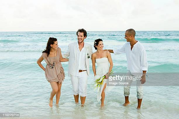 Married couple paddling in sea with friends