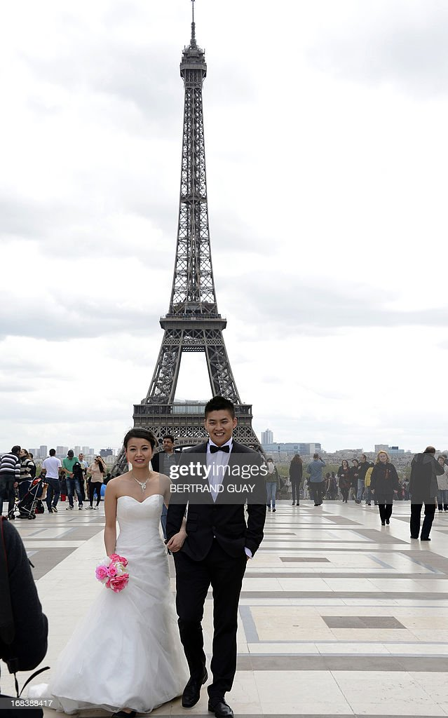 A married couple poses in front of the Eiffel tower, on May 9, 2013 in Paris.