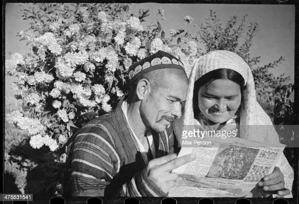 Married couple reading a newspaper circa 1940