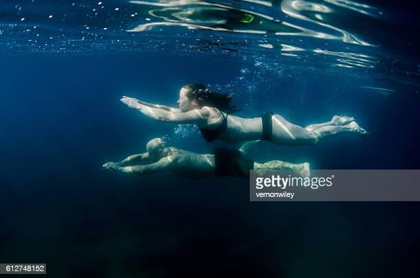 Married couple swimming underwater in deep dark water