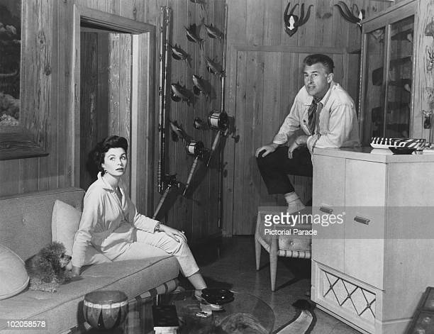 Married English actors Stewart Granger and Jean Simmons at home with their pet poodle circa 1955 On the wall are some of Granger's hunting and...