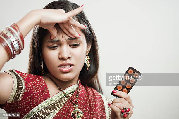 Married Hindu young woman holding head and pills.