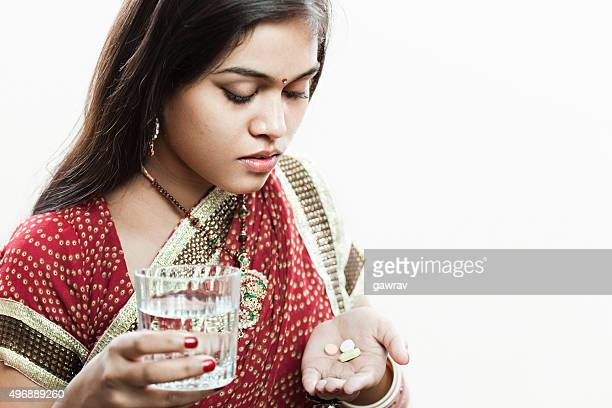 Married Hindu young woman holding pills and glass of water.