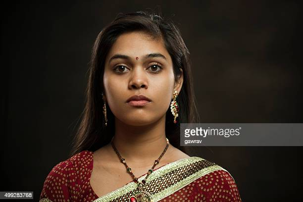 Married Hindu young woman looking at camera with blank expression.