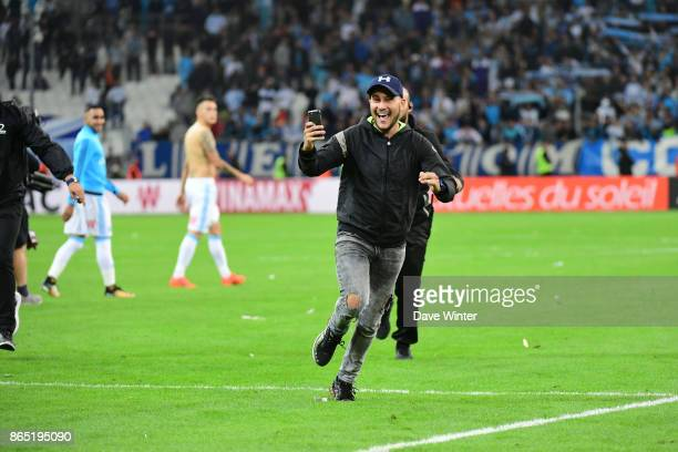 A Marseille fan runs on the pitch and films himself evading security after the Ligue 1 match between Olympique Marseille and Paris Saint Germain at...