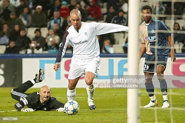 Bolton's forward Stelios Giannakopoulos kicks a ball to score despite Marseille's goalkeeper Fabien Barthez and defender Habib Beye during the UEFA...