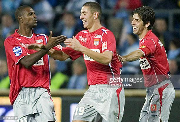 Lyon's French forward Karim Benzema celebrates after he scored a goal with teamates Eric Abidal and Juninho during the French L1 football match...