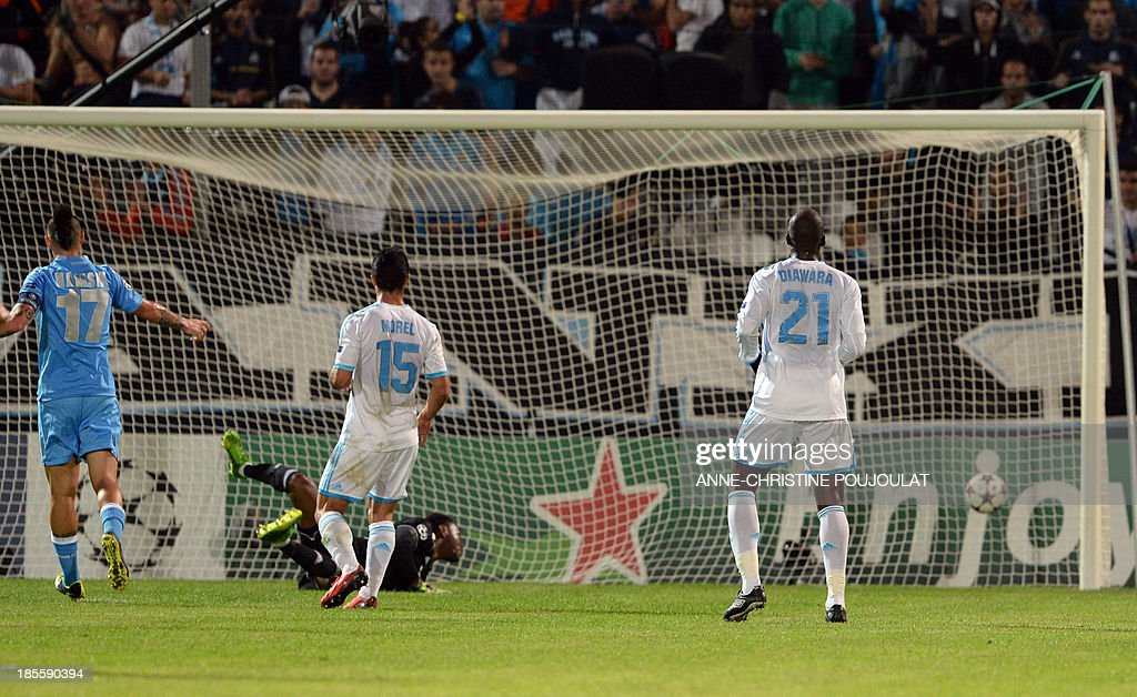 Marseille goalkeeper Steve Mandanda (C) watches the ball enter the goal on October 22, 2013 after a kick by Napoli's Colombian forward Zapata Duvan Esteban during a UEFA Champions League group F football match at the Velodrome stadium in the southern French city of Marseille.